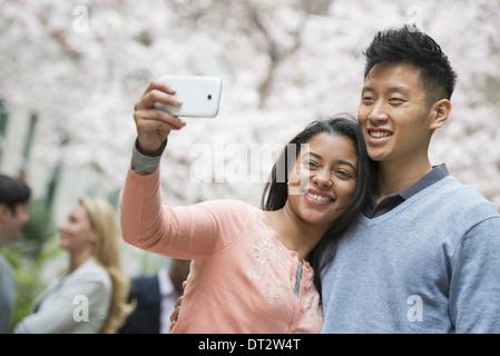 Vista sobre pueblo cityYoung al aire libre en un parque de la ciudad una pareja teniendo un autorretrato o selfy con un teléfono inteligente.