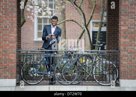 Vista sobre pueblo cityYoung en un parque de la ciudad a un hombre en un traje al lado de un parque de bicicletas en una acera con su teléfono inteligente.