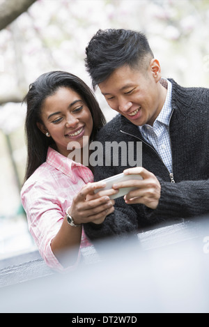 Vista sobre pueblo cityYoung al aire libre en un parque de la ciudad una pareja al lado mirando hacia un teléfono inteligente.