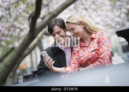 Vista sobre pueblo cityYoung parque al aire libre, una joven mujer y hombre sentado al lado mirando hacia un teléfono inteligente.
