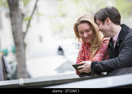 Vista sobre pueblo cityYoung al aire libre en un parque de la ciudad Dos personas sentadas al lado mirando hacia un teléfono inteligente.