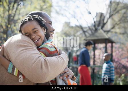 Una familia junto a un padre abrazando a su hijo