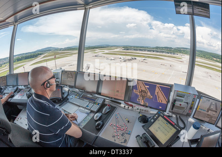 Un controlador de tráfico aéreo en la torre de control del aeropuerto internacional de Zúrich Kloten/está supervisando el aeródromo del aeropuerto.