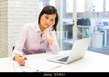 Cansado empresaria en mesa de trabajo con ordenador y papel