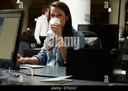 Mujer joven beber café en la oficina