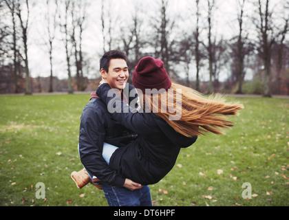 Apuesto joven llevando a su novia en el parque. Pareja joven asiática divirtiéndose al aire libre. Foto de stock