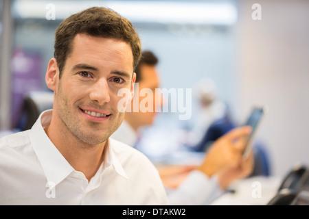 Retrato del empresario alegre en oficina, mirando la cámara