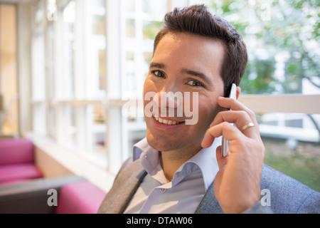 Feliz sonriente joven empresario en el teléfono en la oficina, mirando la cámara Foto de stock