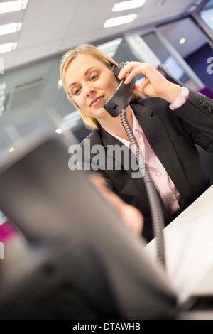 Mujer joven en un tel fono en el escritorio en la oficina for Telefono de la oficina