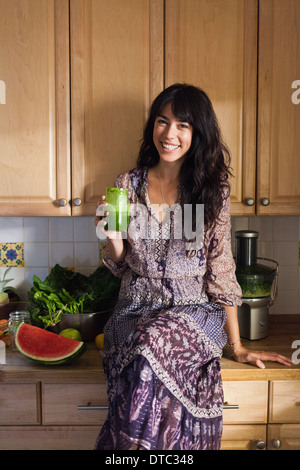Joven en cocina con jugo de vegetales