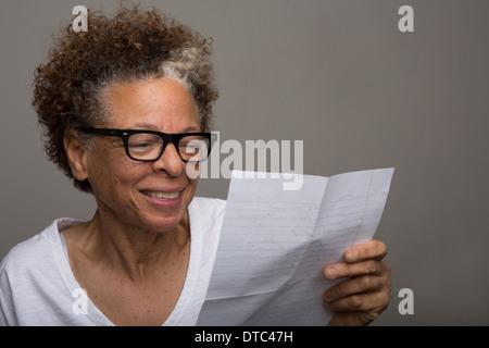 Retrato de estudio de feliz altos mujer leyendo una carta