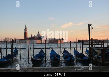 Venecia, Italia, con un trasfondo de San Giorgios, góndolas yacen todavía al final del día. Es una escena que caracteriza a Venecia