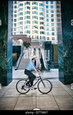 Hombre de negocios caucásico, montando bicicleta fuera highrise