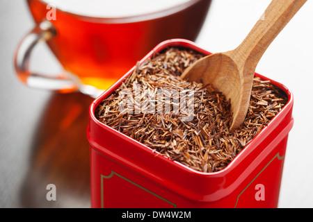 En el té de rooibos tin box y cuchara de madera closeup