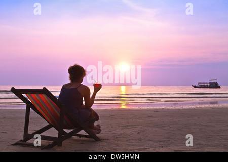 Mujer de mediana edad con cocktail disfrutar del atardecer en la playa