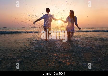 Feliz pareja disfrutar del atardecer en la playa