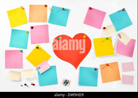 Varios colores en blanco las notas en papel, suministros de oficina y papel rojo corazón aislado sobre fondo blanco.