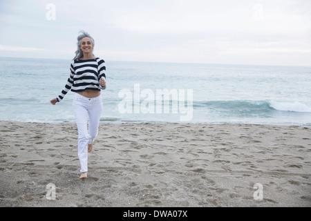 Mujer madura, corriendo en la playa, Los Ángeles, California, Estados Unidos.