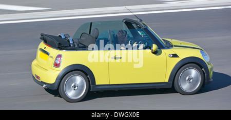 Dos puertas BMW Mini Cooper descapotable coche convertible con la mujer la conducción en autopista, Essex, Inglaterra