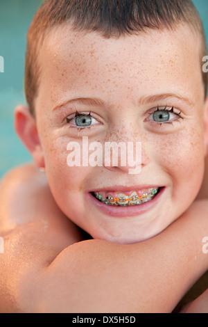 Chico de ojos azules con llaves y pecas en piscina, gran sonrisa, retrato, cerrar
