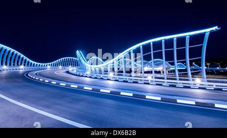 Iluminado puente arquitectónico moderno en el hipódromo de Meydan, en Dubai, Emiratos Árabes Unidos Foto de stock