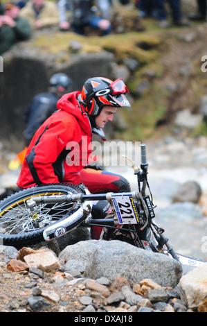 Un hombre sentado junto a una senderos bicicleta junto a un río, durante los ensayos SSDT.