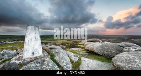 Un punto Trig para asignar la triangulación bajo un cielo tormentoso en la parte superior de Helman Tor en Cornwall.