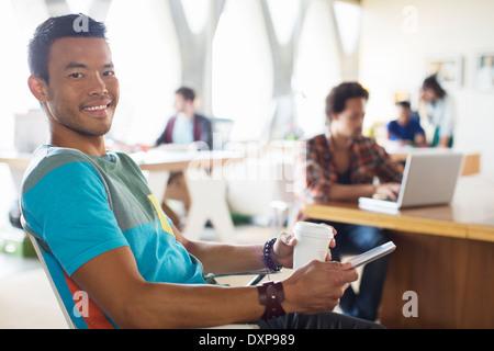 Retrato de sonriente empresario casual bebiendo café y utilizando tablet digital en Office