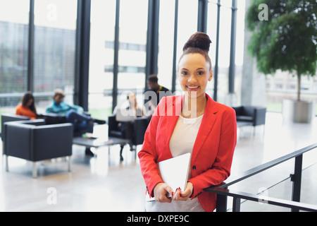 Bastante joven sosteniendo un portátil de pie por una baranda mirando a la cámara sonriendo. Joven Empresaria afroamericana.