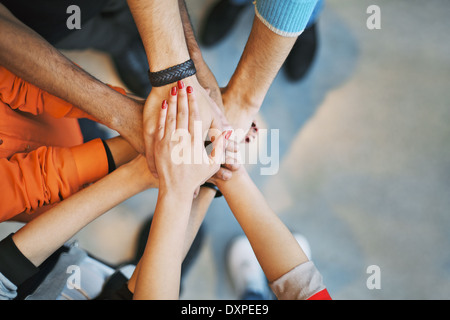 Grupo multiétnico de gente joven poniendo sus manos en la parte superior de cada uno. Cerrar imagen de jóvenes estudiantes manos de apilamiento.