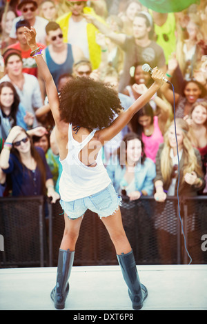 Fans aclamando a la mujer realiza en el escenario