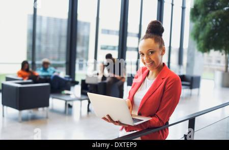 Hermosa joven con un portátil en la oficina moderna. La empresaria afroamericana por una verja permanente con personas trabajando.