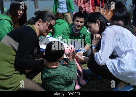 Nanjing, China la provincia de Jiangsu. 2 abr, 2014. Los voluntarios acompañan a un niño autista durante un evento de bienestar infantil en Nanjing, capital de la oriental provincia de Jiangsu de China, 2 de abril de 2014. El miércoles, el evento fue organizado por el centro de formación infantil local para conmemorar el séptimo día mundial de concienciación del autismo. Los organizadores celebraron una serie de actividades interactivas con la esperanza de aumentar la preocupación social para niños con autismo. © Shen Peng/Xinhua/Alamy Live News Foto de stock
