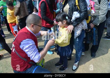 Nanjing, China la provincia de Jiangsu. 2 abr, 2014. Un voluntario une un blue ribbon de sensibilización, un símbolo de preocupación, a la muñeca de una niña con autismo durante un evento de bienestar infantil en Nanjing, capital de la oriental provincia de Jiangsu de China, 2 de abril de 2014. El miércoles, el evento fue organizado por el centro de formación infantil local para conmemorar el séptimo día mundial de concienciación del autismo. Los organizadores celebraron una serie de actividades interactivas con la esperanza de aumentar la preocupación social para niños con autismo. © Shen Peng/Xinhua/Alamy Live News Foto de stock