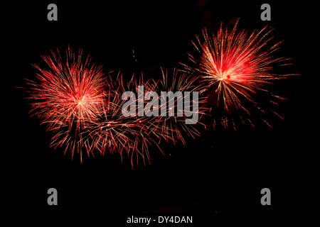 Ráfagas de color rojo y naranja Fireworks contra un cielo negro
