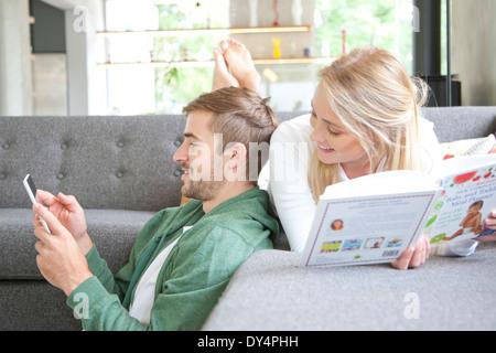 Hombre utilizando el smartphone y Mujer leyendo el libro sobre el sofá Foto de stock