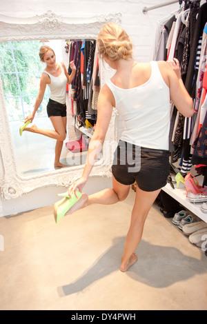 Mujer en el armario mirando en el espejo probándose zapatos