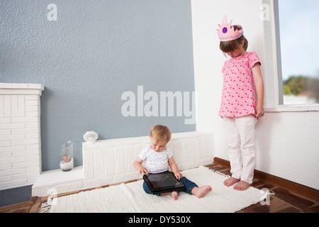Chica viendo más baby boy jugando tableta digital