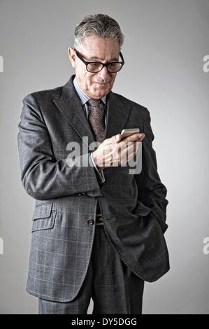 Hombre senior a través de teléfono móvil Foto de stock
