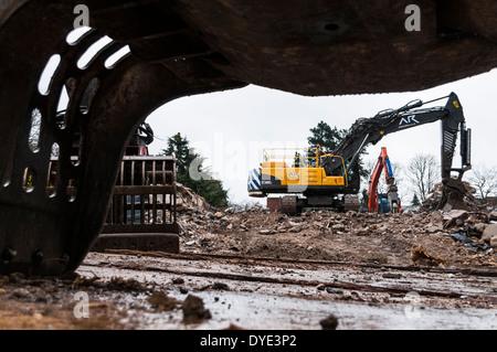 Vista desde debajo del ángulo bajo un accesorio de pinza de dos excavadoras de demolición