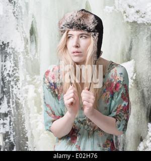 Mujer rubia delante de montañas cubiertas de hielo vistiendo ropa de verano e invierno hat Foto de stock