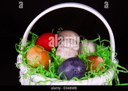 Canasta de mimbre blanco multicolor lleno de huevos de Pascua