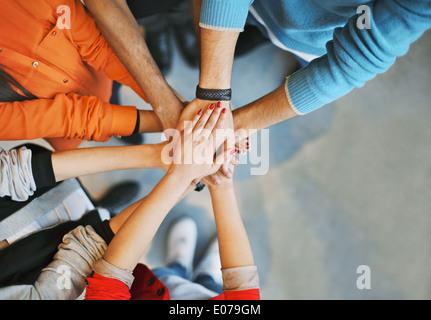 Vista superior de la imagen de un grupo de jóvenes poniendo sus manos juntas. Amigos con pila de manos mostrando la unidad.