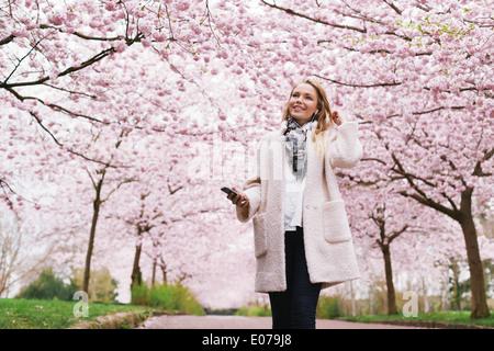 Mujer sonriente con el teléfono móvil para escuchar música en el parque. Mujeres jóvenes y atractivas en spring blossom jardín. Foto de stock