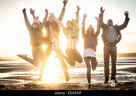 Cinco amigos adultos saltando el aire en la playa
