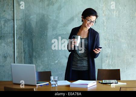 Joven Empresaria mirando smartphone en Office