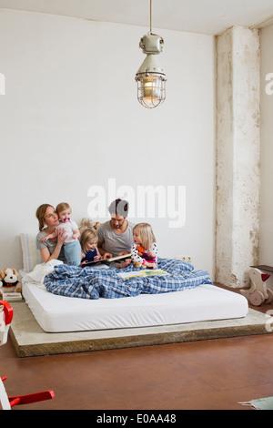 Familia con tres hijas leer libros en la cama