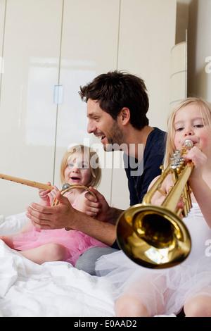 El padre y sus dos hijas reproduciendo música