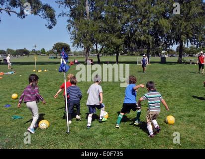 Los niños practicar rebotando una pelota de fútbol en un campamento de verano en el parque