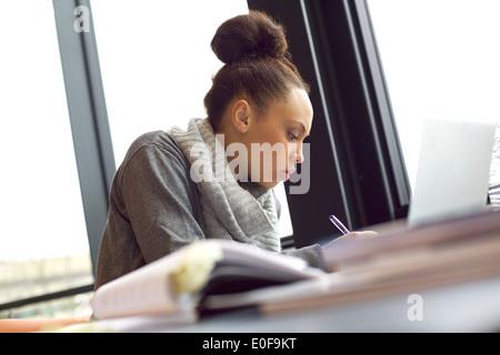 Joven afroamericana tomando notas de libros para su estudio. Sentado a la mesa con los libros y el portátil para obtener información.
